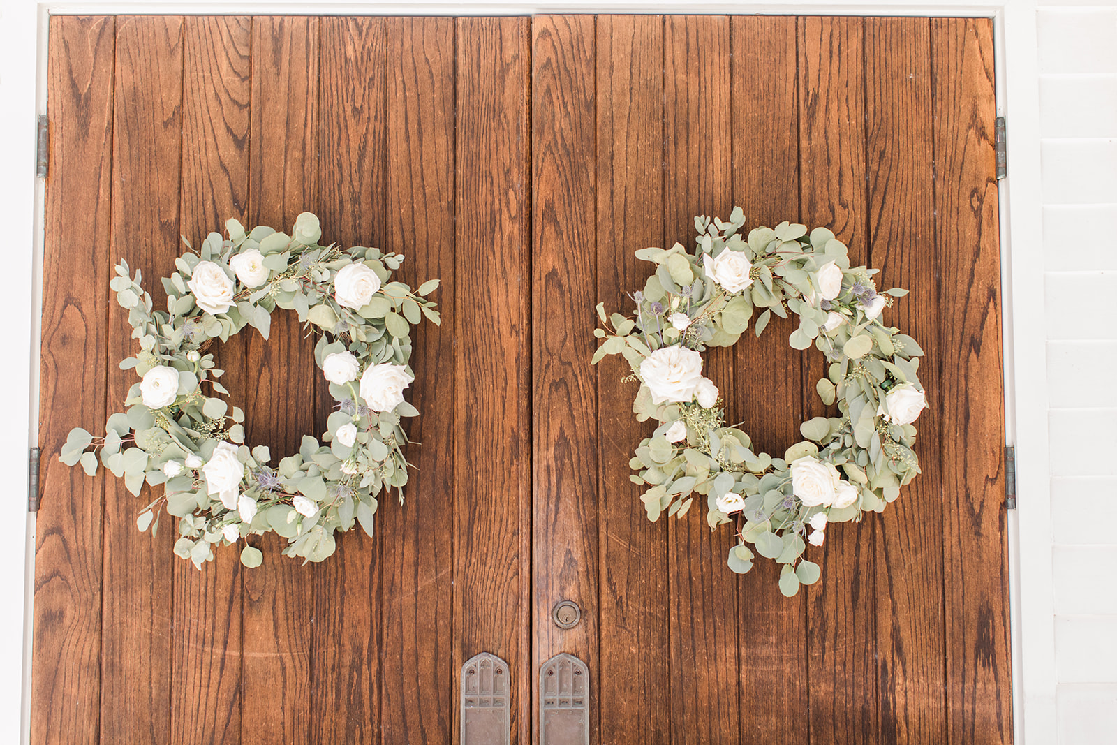 eucalyptus and ivory flower wreaths on doors at St. Francis at the Point