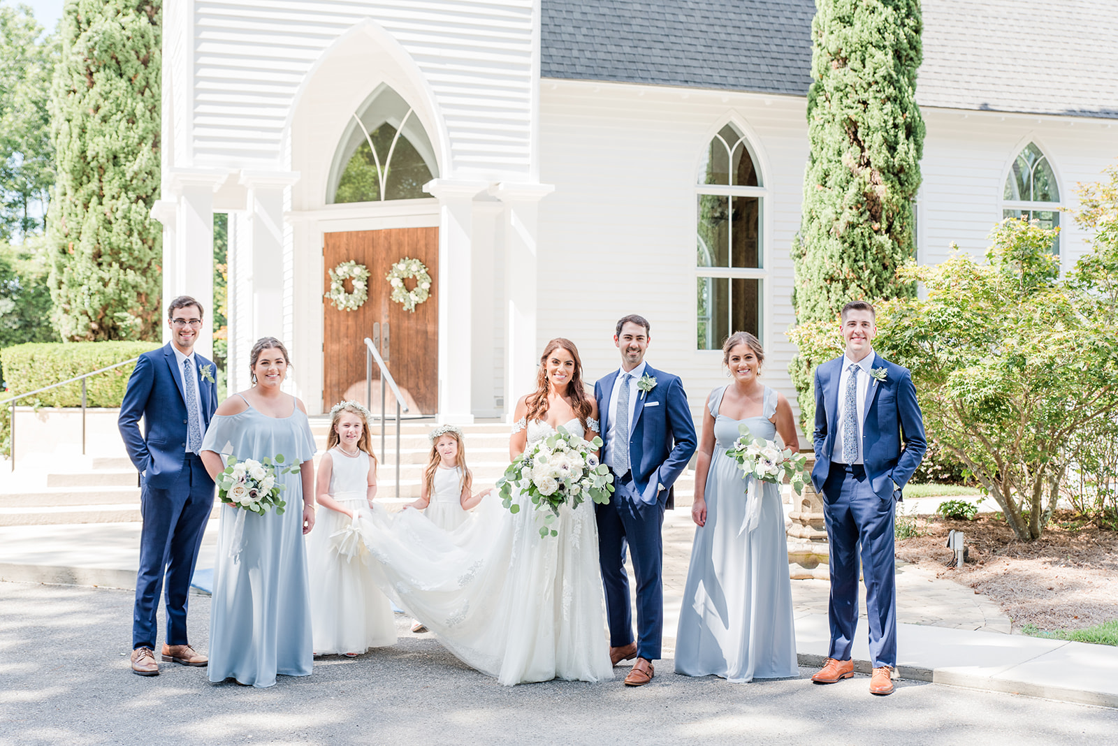 bridal party poses outside St. Francis at the Point