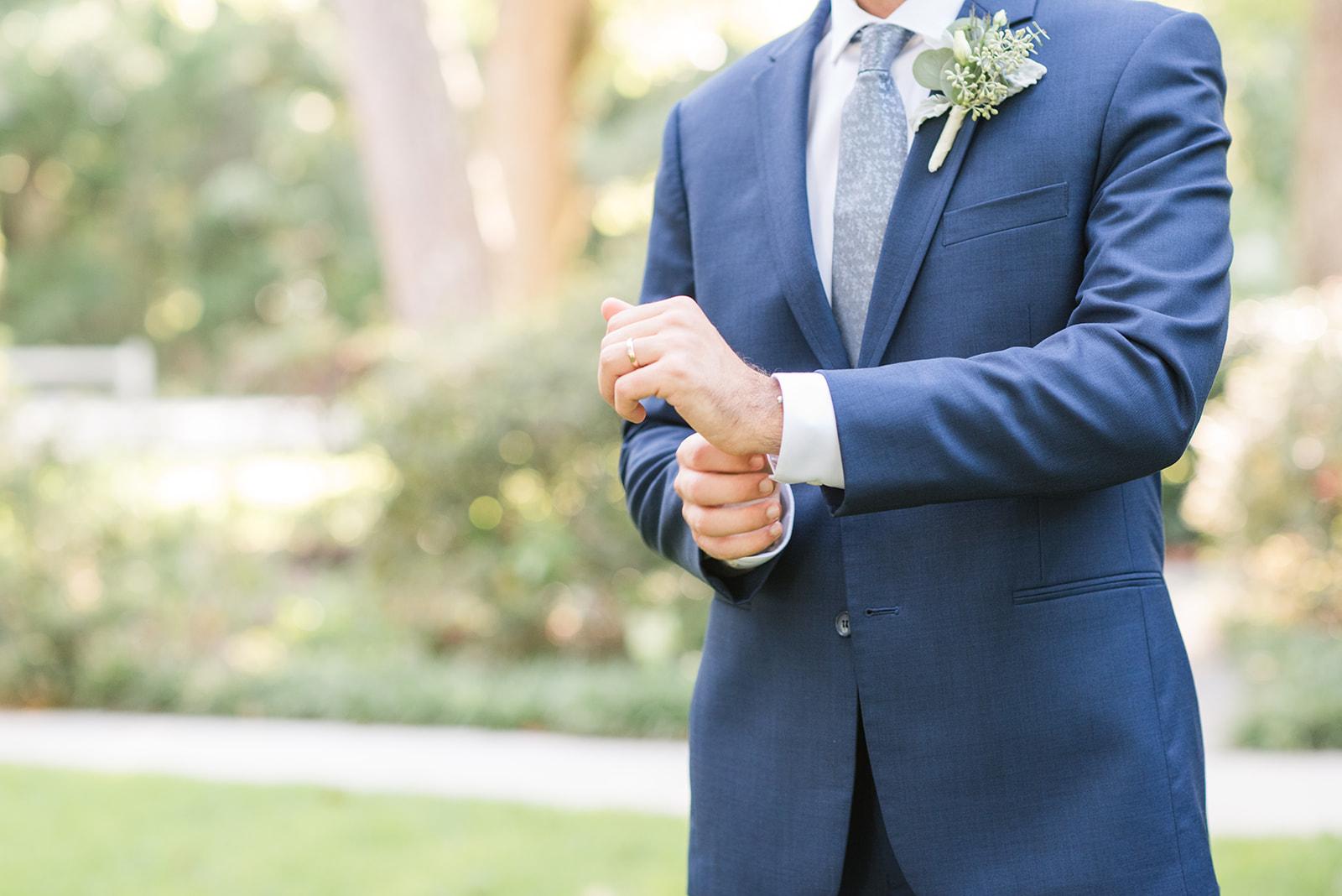 groom adjusts cufflink during Fairhope AL destination wedding photos