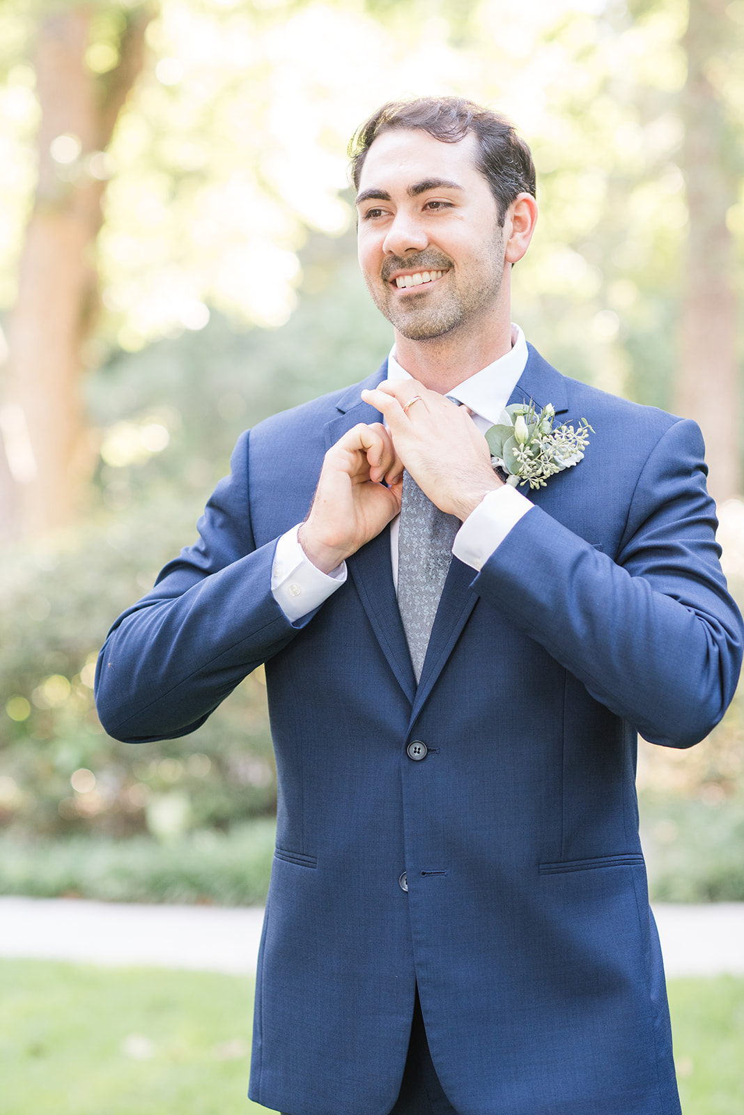 groom adjusts tie with navy suit jacket in Fairhope AL