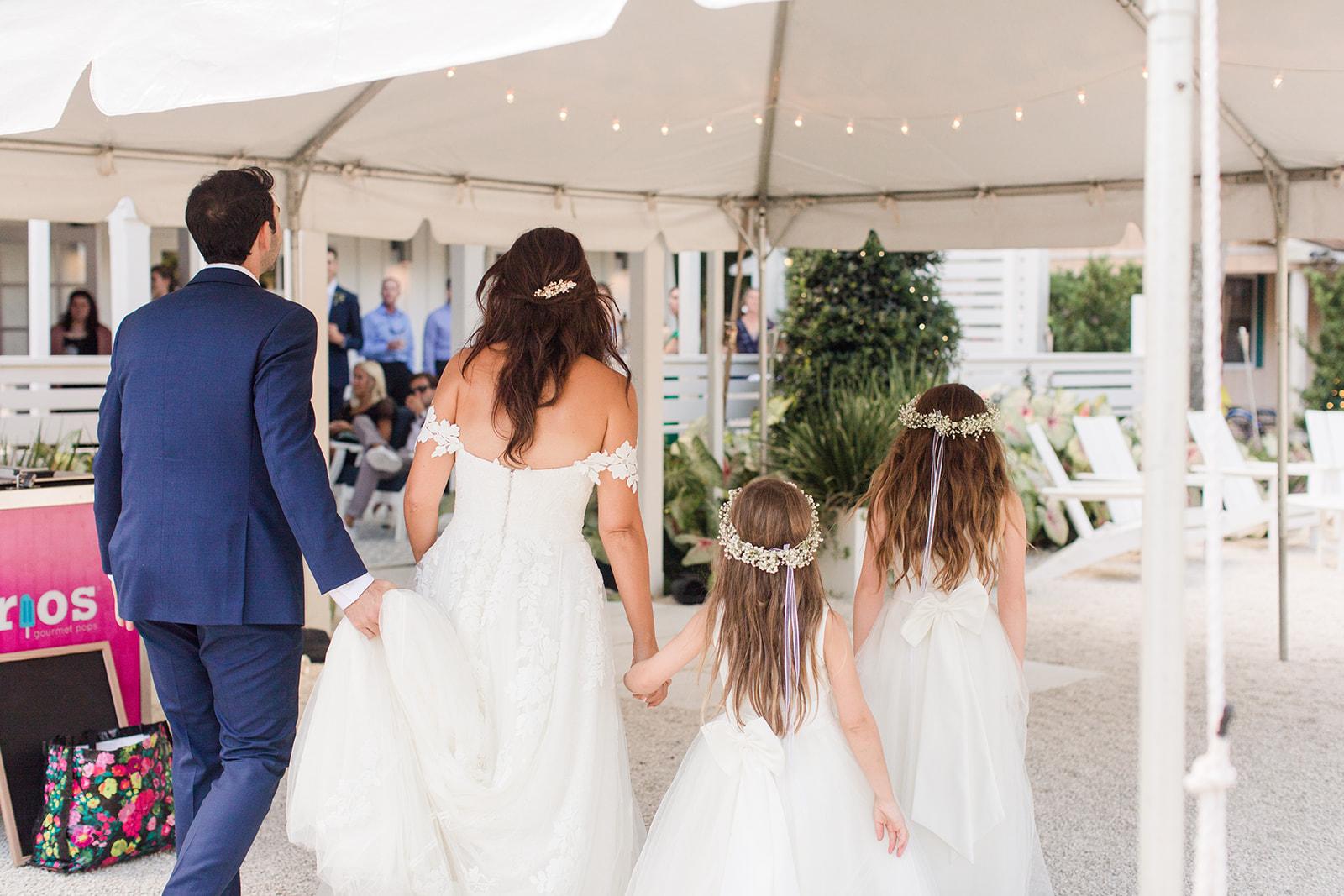 flower girls walk with bride into wedding reception