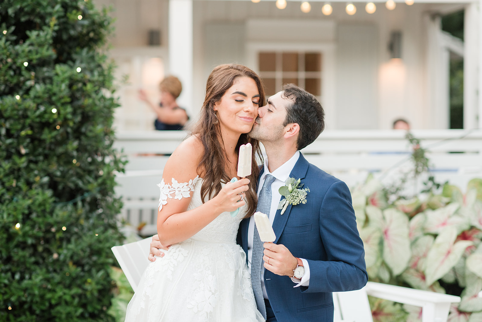 groom kisses bride while enjoying popsicles at Little Point Clear