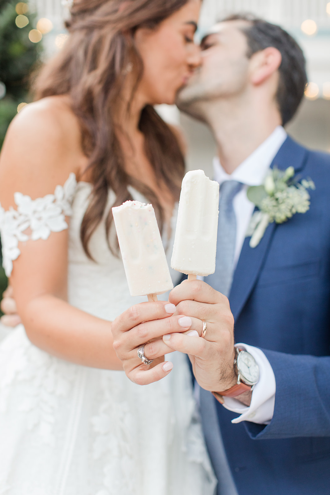 bride and groom hold popsicles, showing off wedding rings