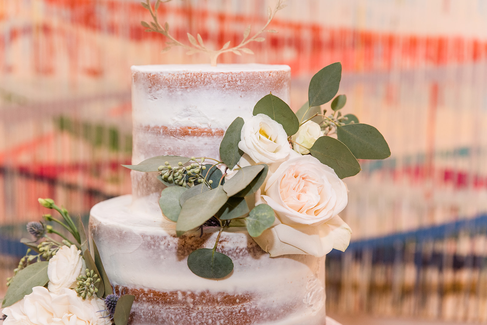 naked wedding cake with floral accents