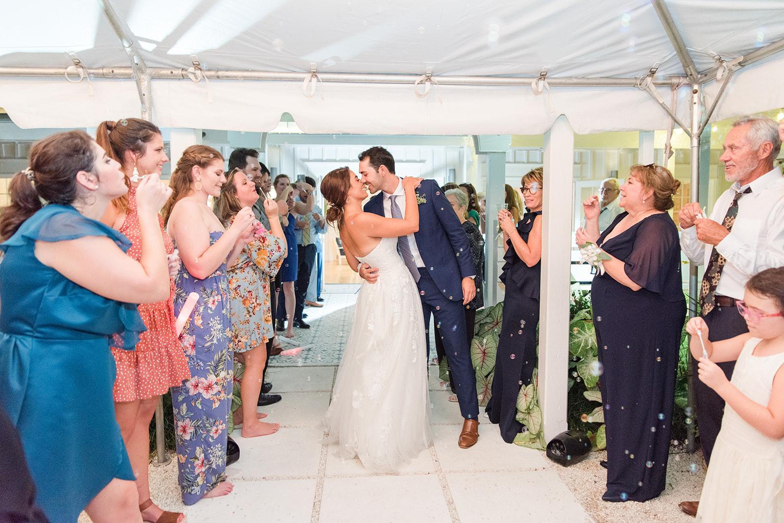 newlyweds kiss during bubble exit at Fairhope AL destination wedding reception