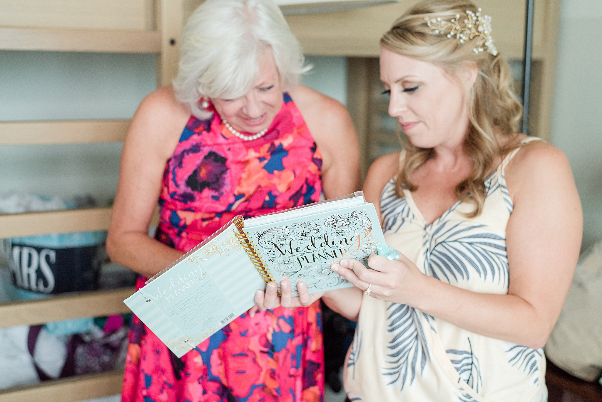 bride shows mother planning notebook before wedding