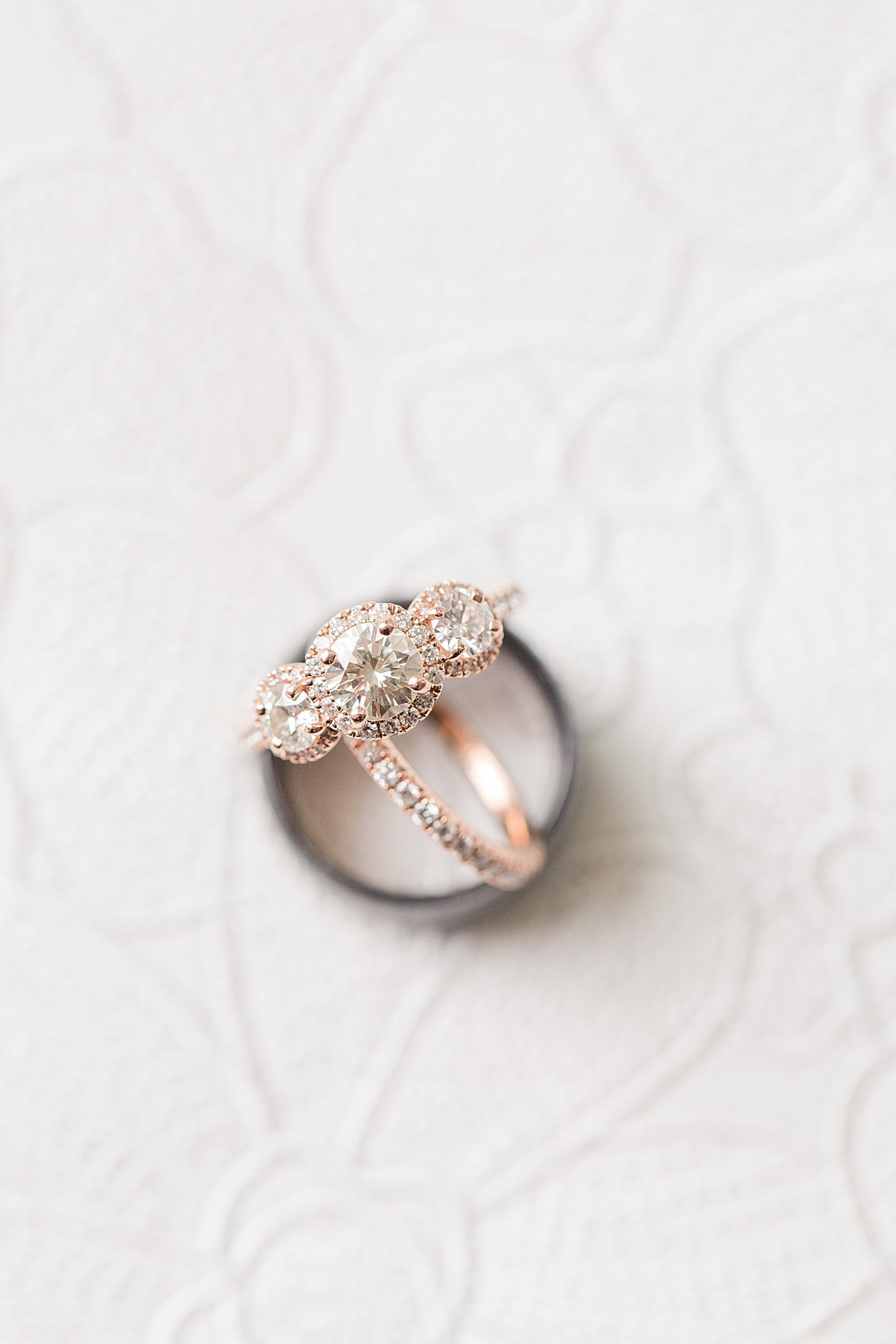 wedding bands sit on lace of wedding gown