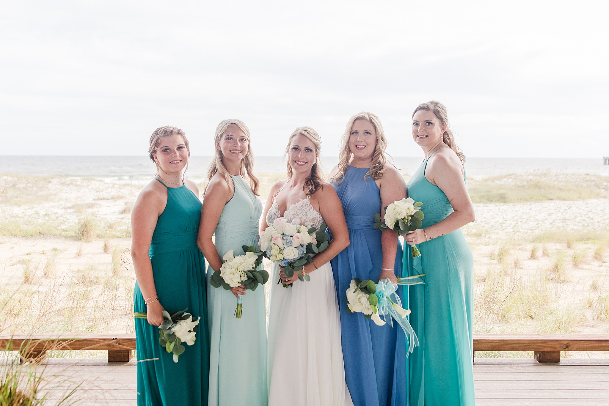 bride poses with bridesmaids in blue and green gowns