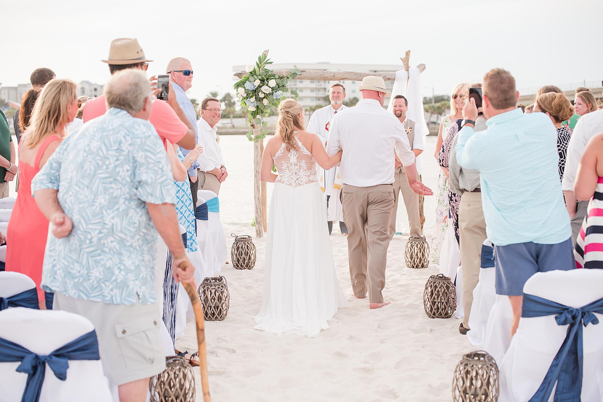 bride walks down the aisle on beach