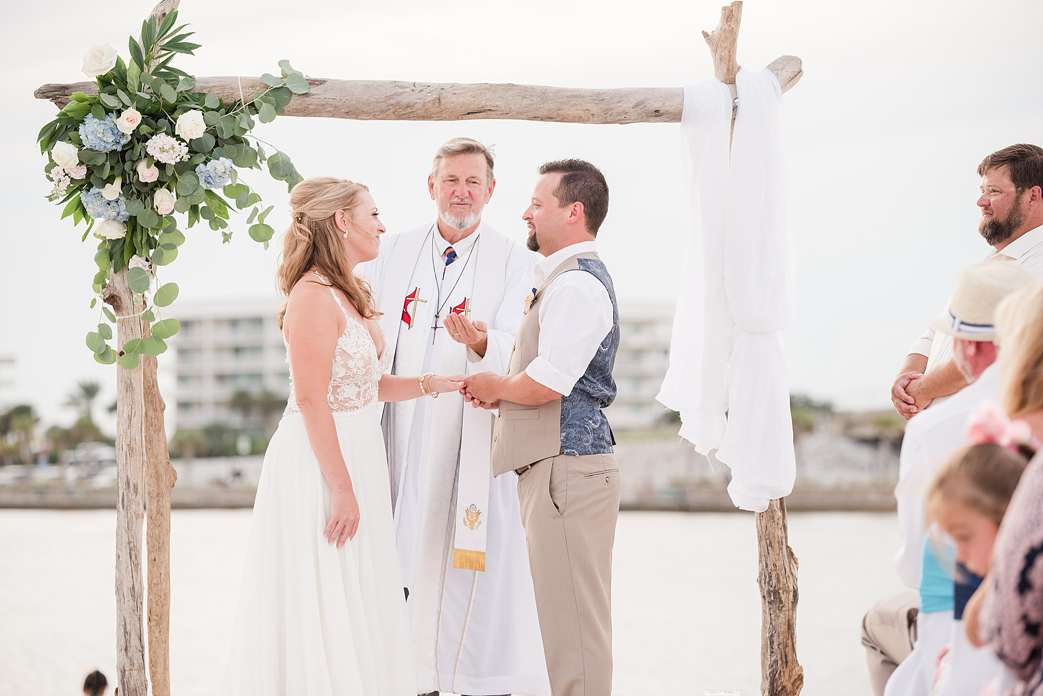 groom gives bride ring during beach wedding