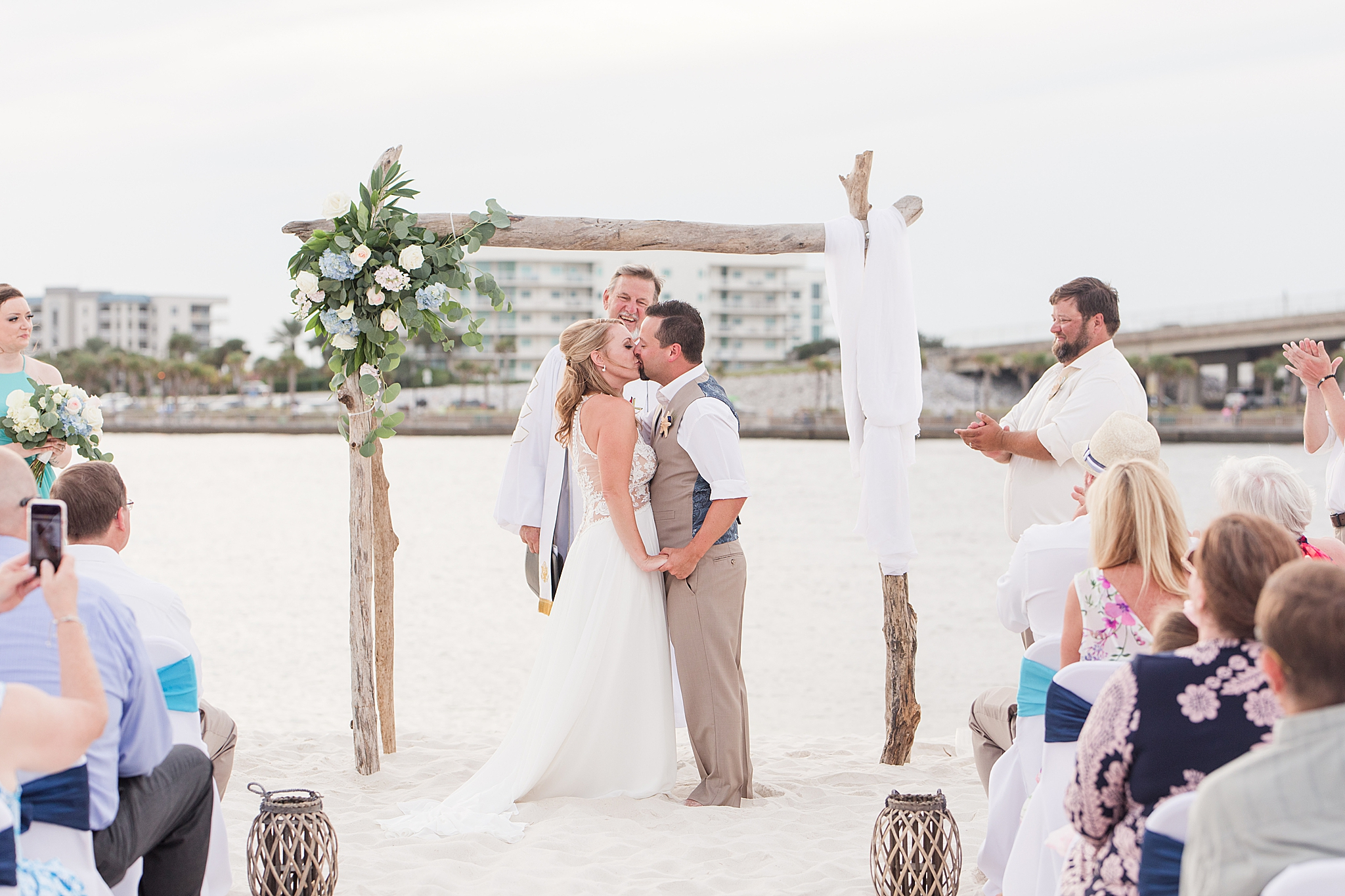 bride and groom kiss on the beach during wedding ceremony