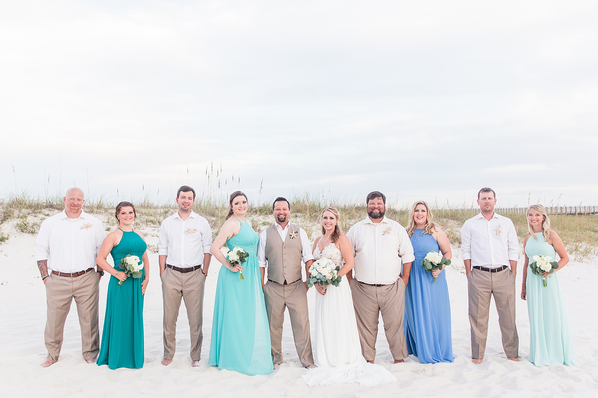 bridal party in sea green and blue pose on Gulf Shores beach