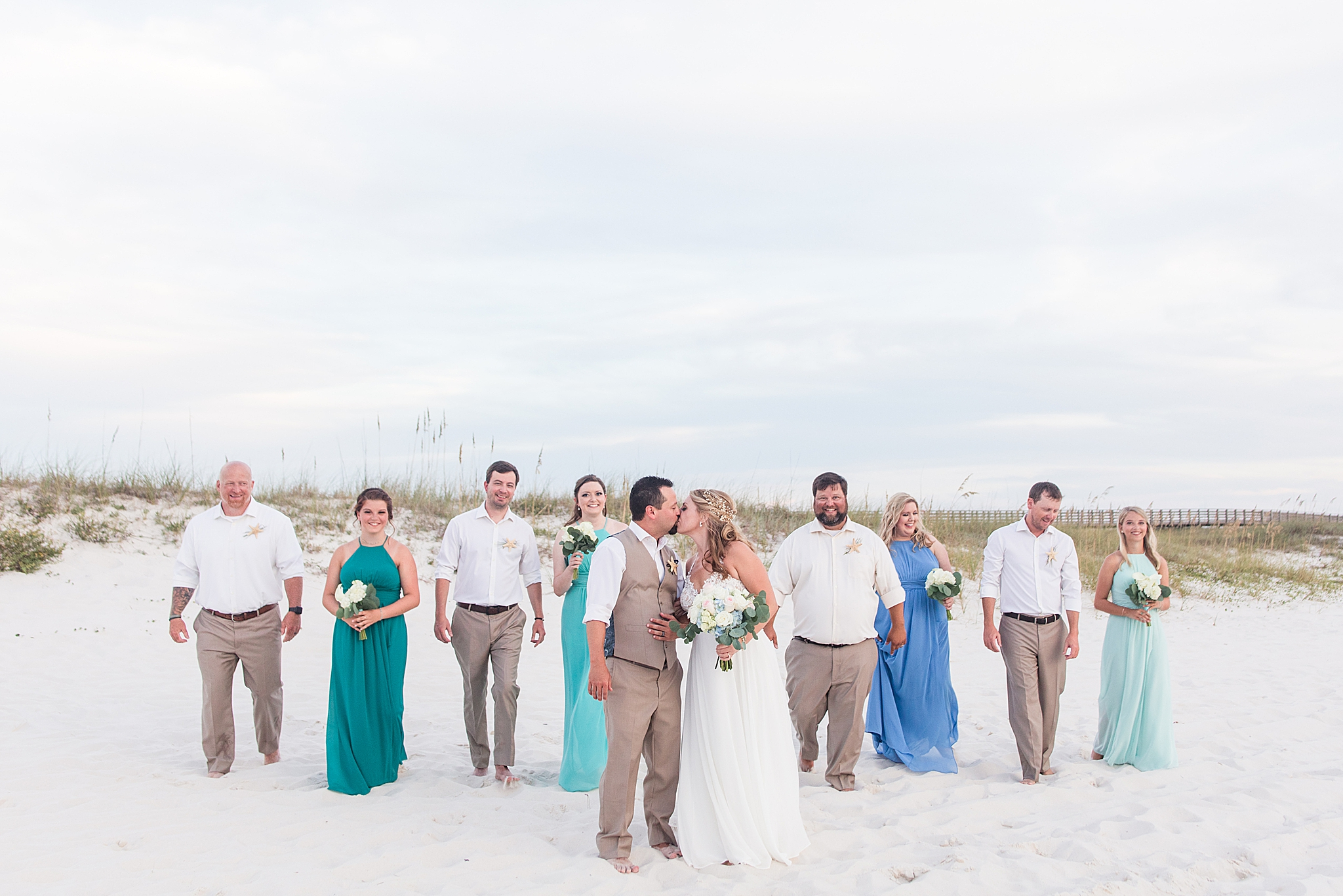 bridal party walks with bride and groom no the beach