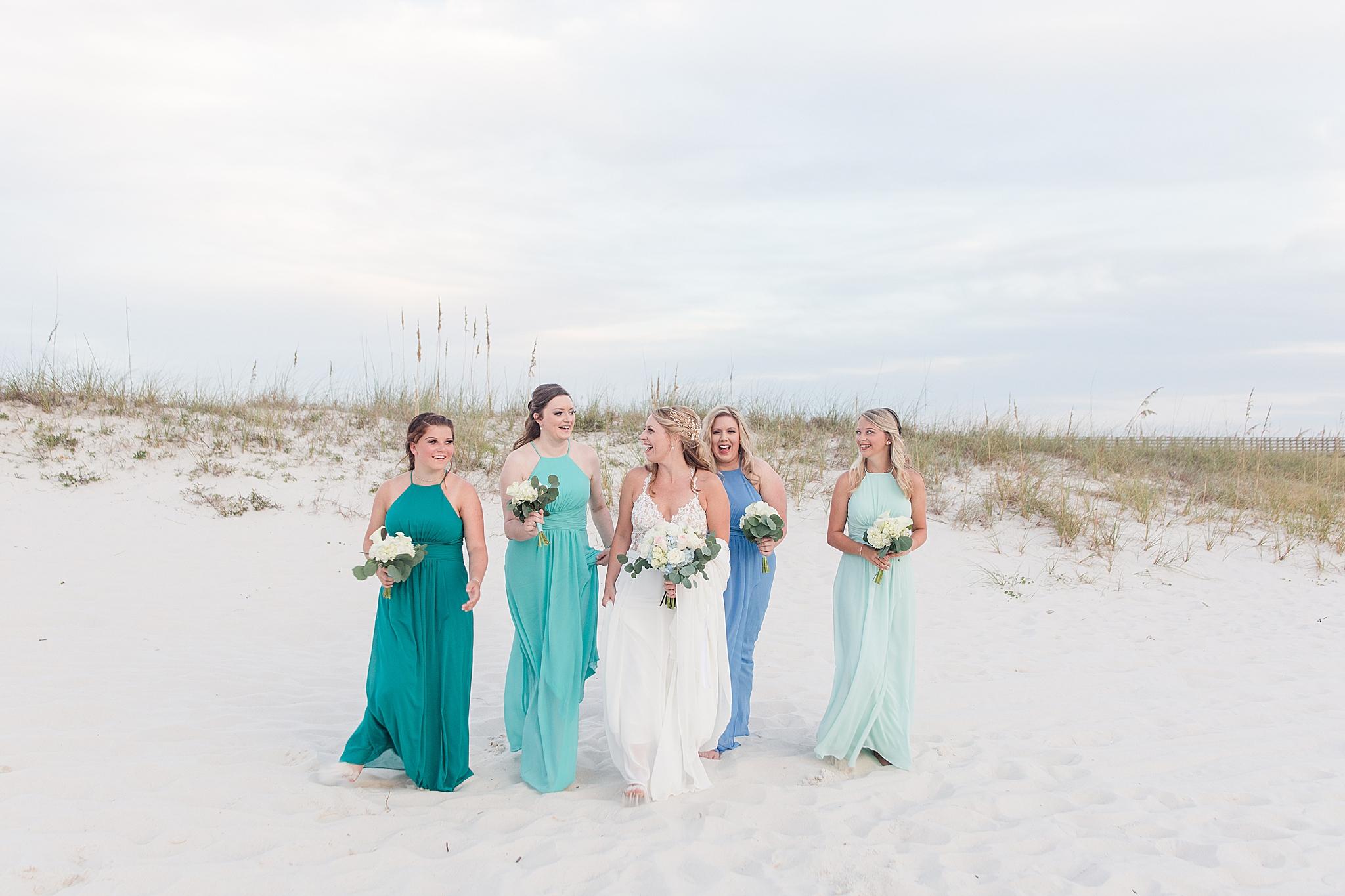 bridesmaids walk with bride along sand dunes