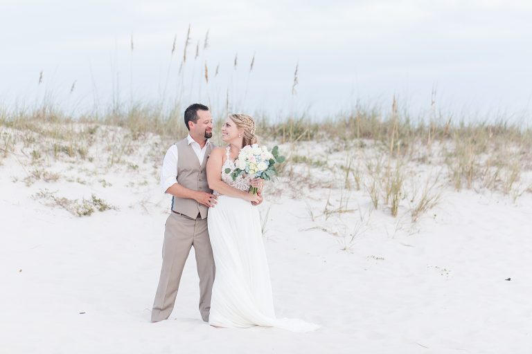 groom holds bride by sand dunes in Alabama