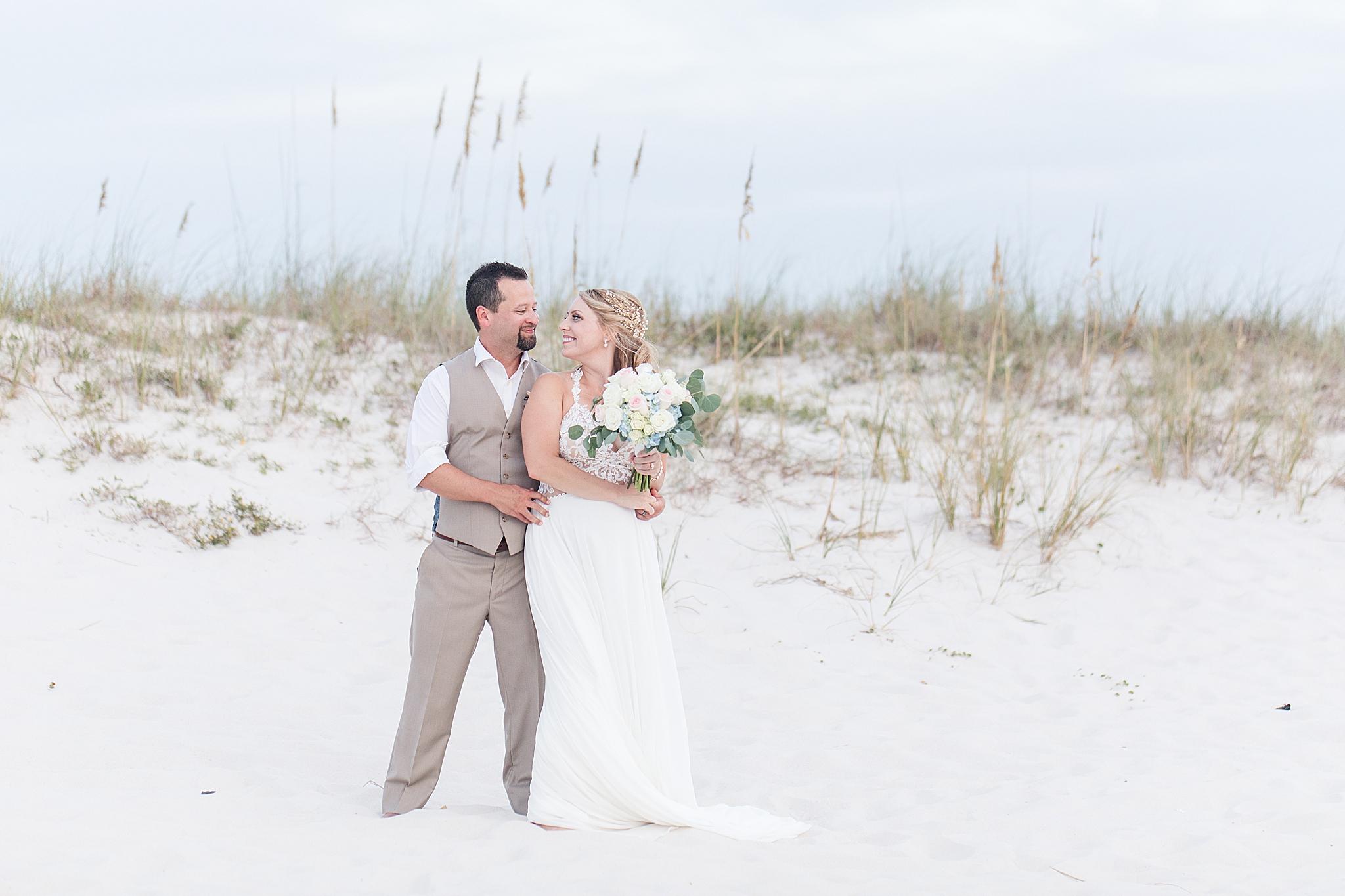 groom holds bride by sand dunes in Alabama