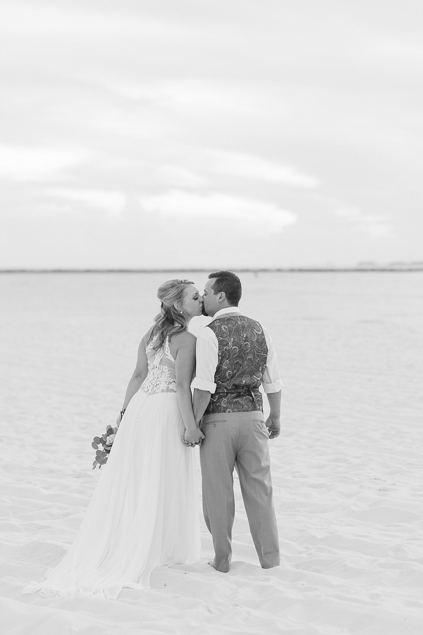 bride and groom kiss along oceanfront on wedding day