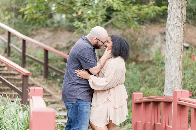 groom kisses bride on bridge in Japanese garden