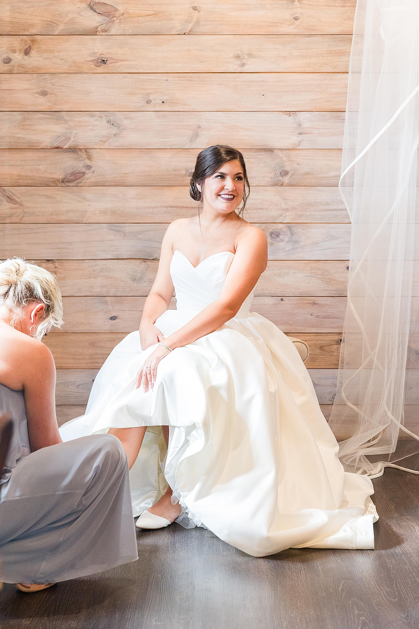 bride prepares for AL wedding with bridesmaid