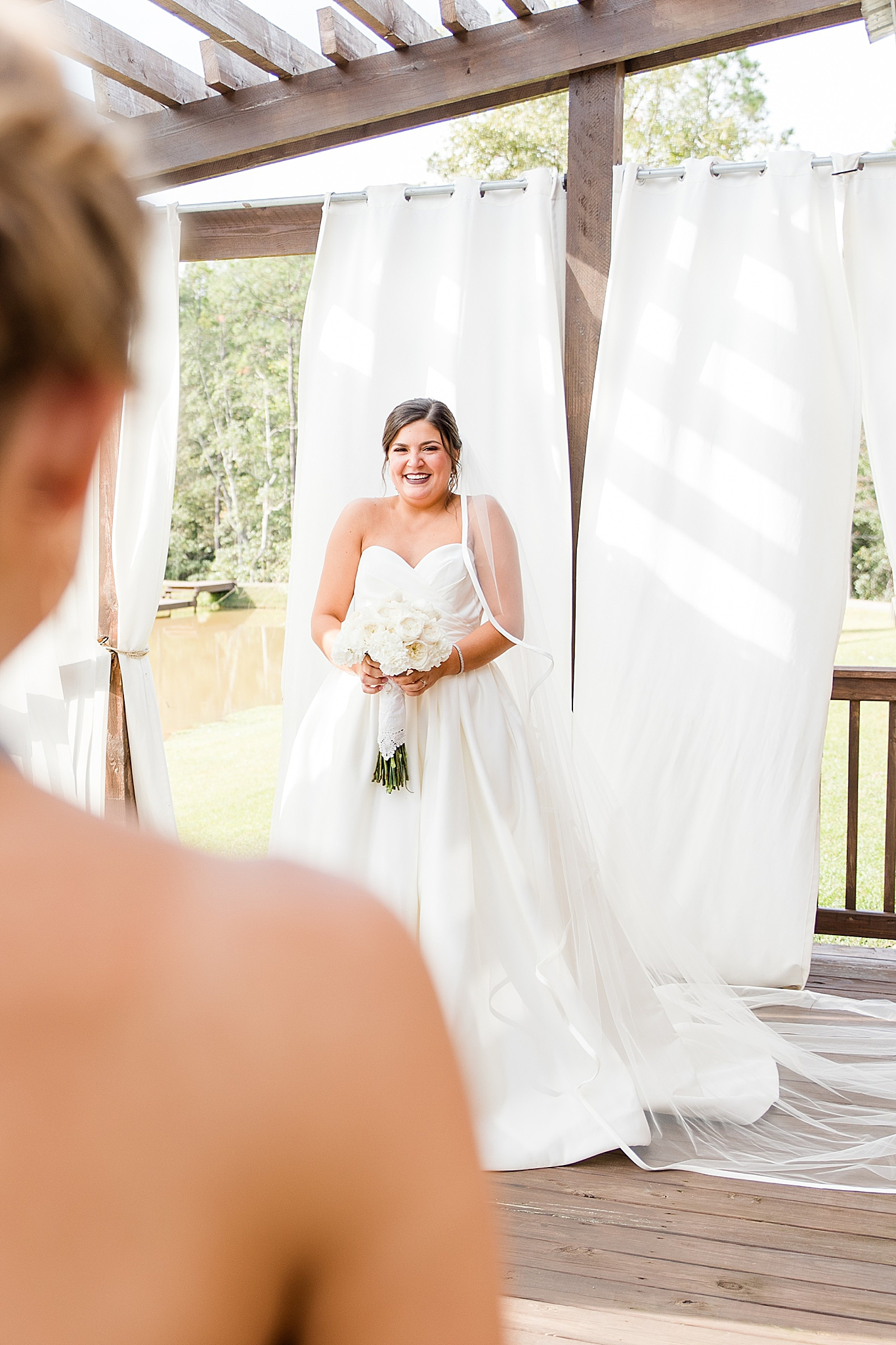bride smiles at bridesmaids during first look