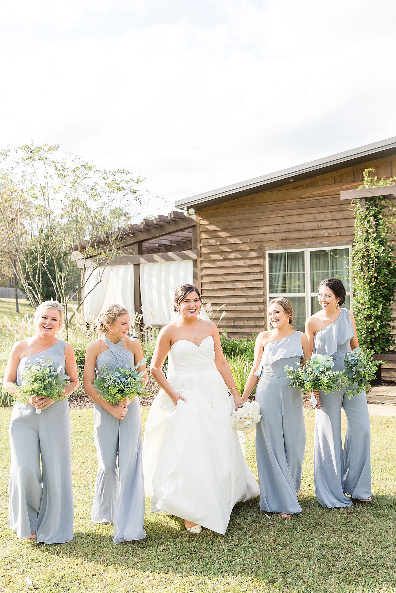 bridesmaids in dusty blue walk with bride at Izenstone