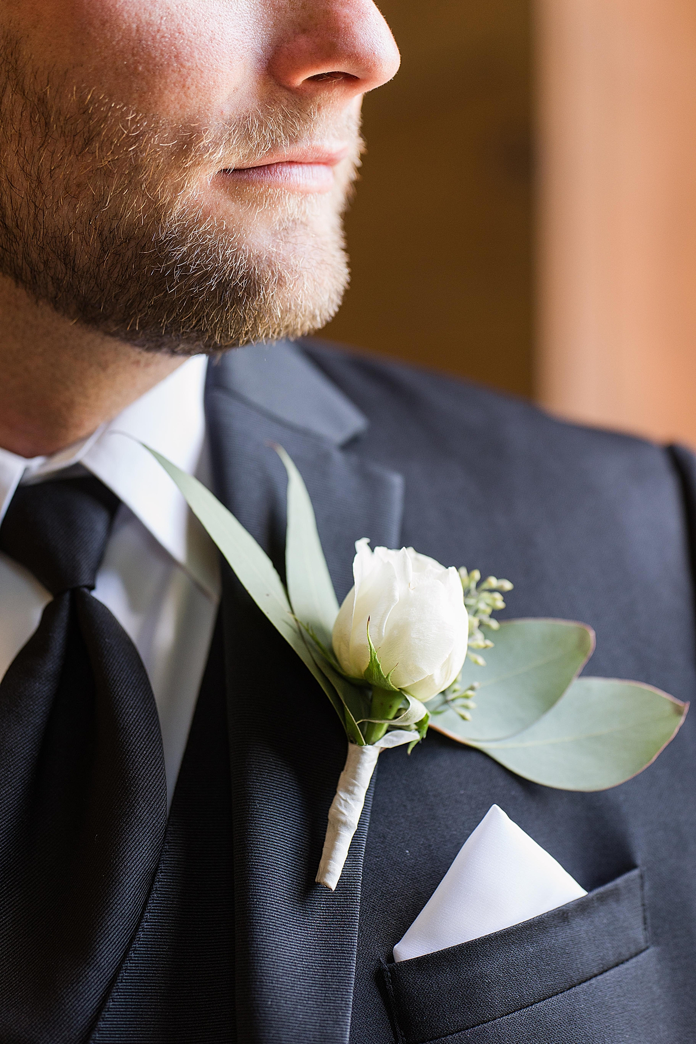 groom poses with ivory rose boutonnière