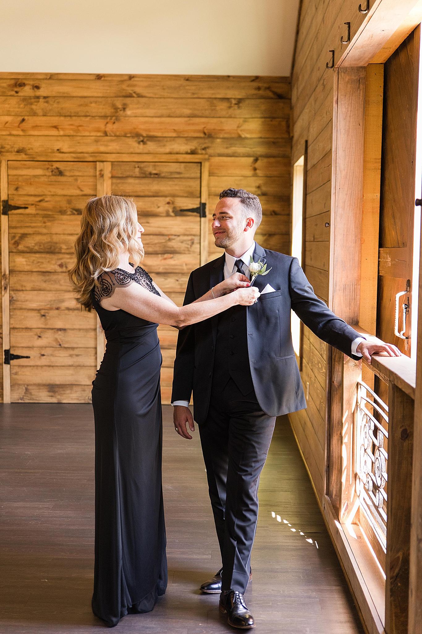 mother of groom adjusts boutonnière