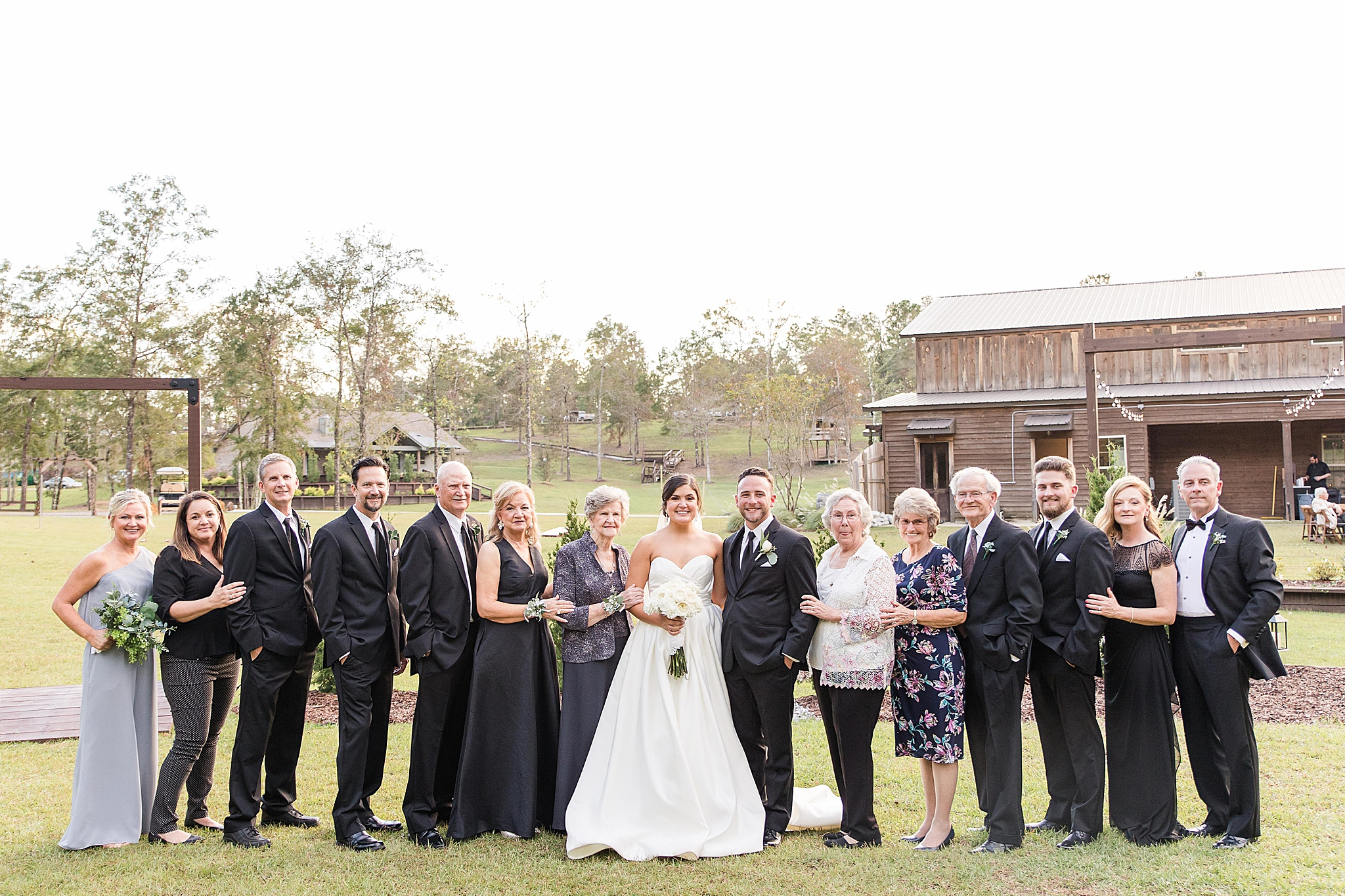 bride and groom pose with family after Spanish Fort AL wedding