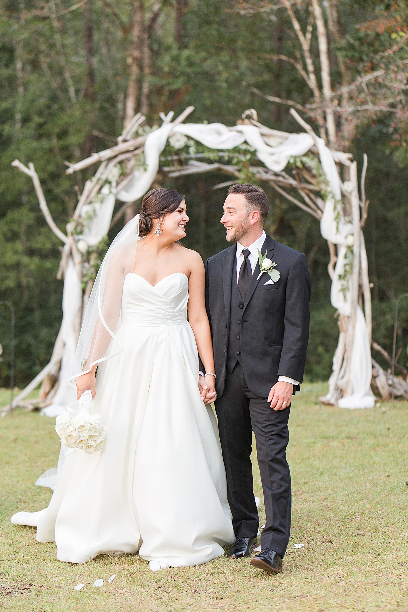 bride and groom walk away from rustic arbor at Izenstone