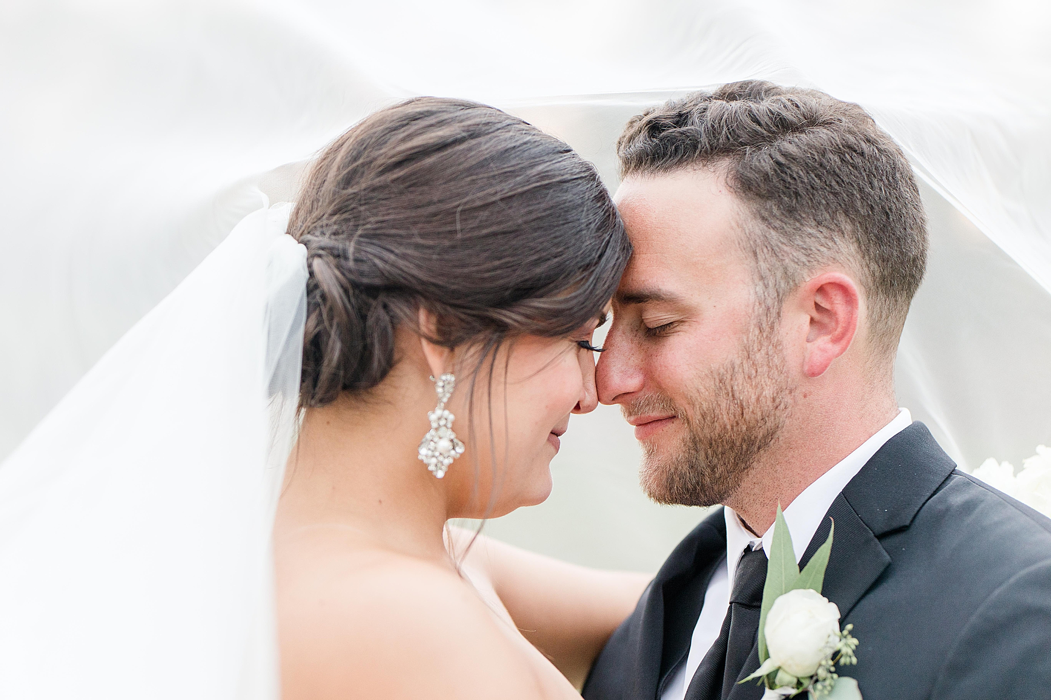 bride and groom stand nose to nose under wedding veil
