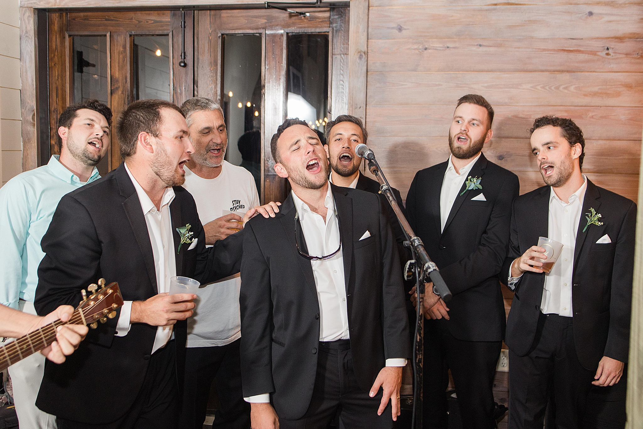 groom and groomsmen sing with band during AL wedding reception