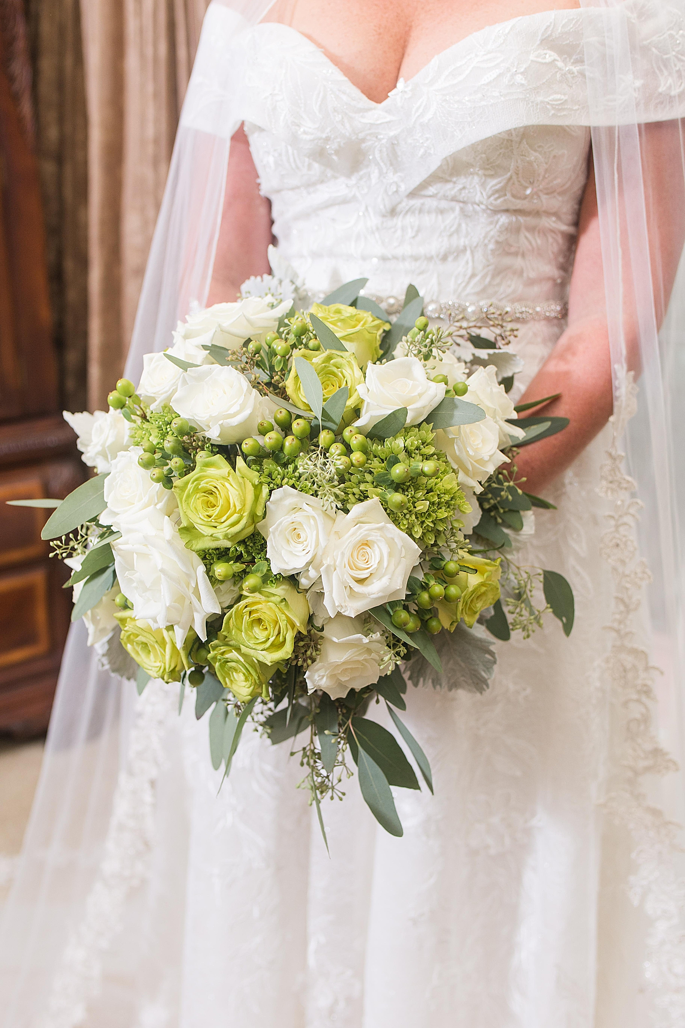 bride holds bouquet of green and white flowers