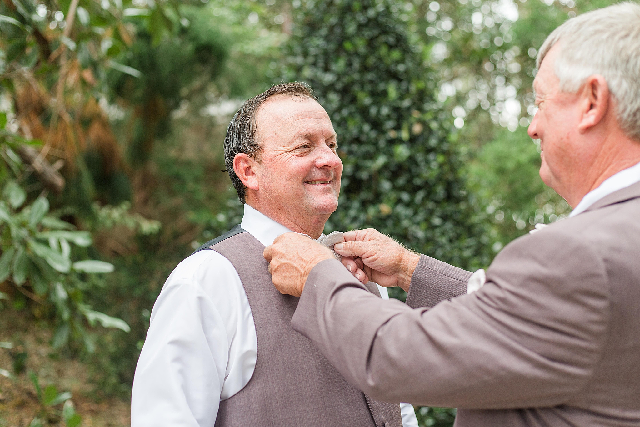 father of groom adjusts tie for groom, tips for groom and groomsmen attire
