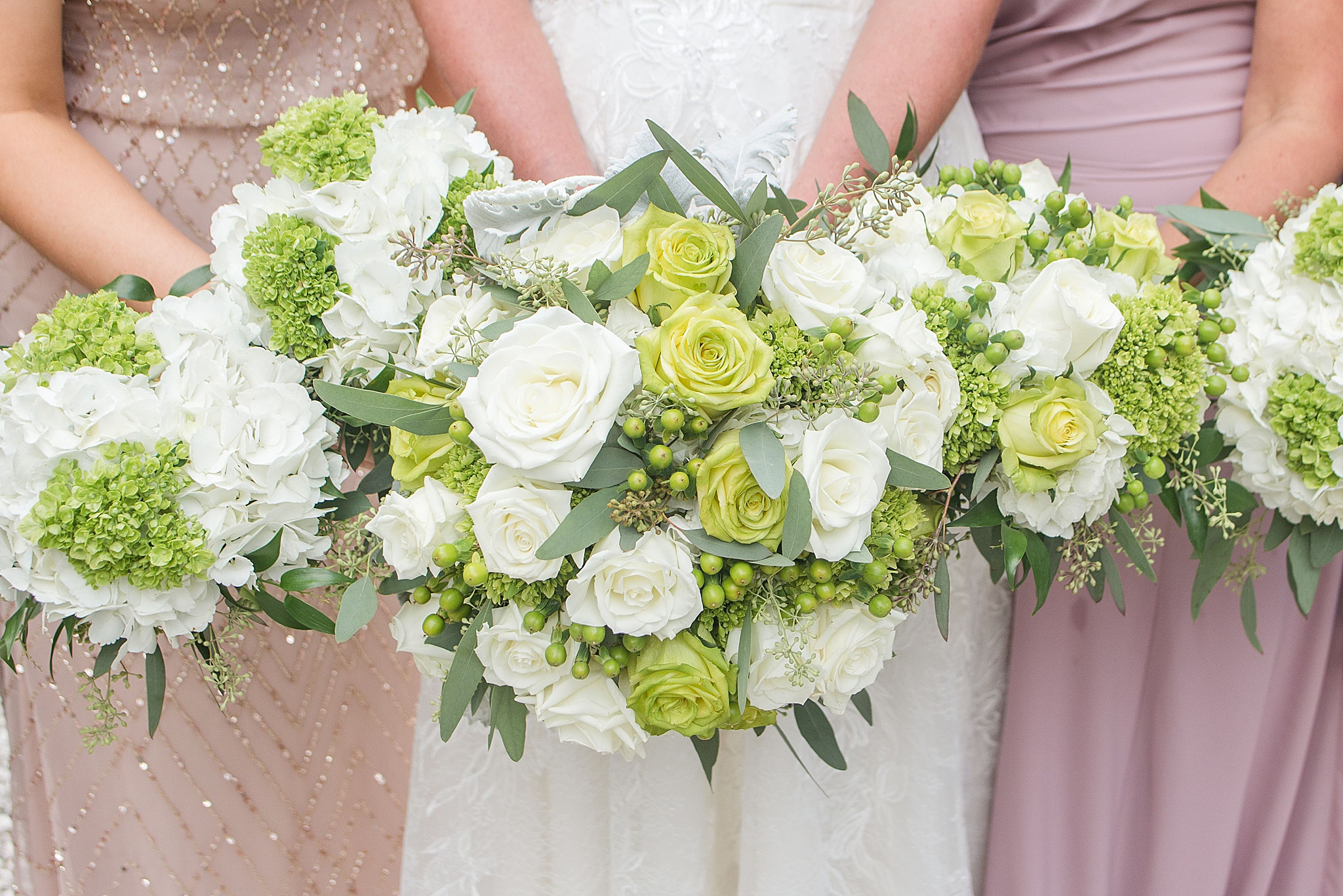 bride and bridesmaids hold bouquet of white and green flowers