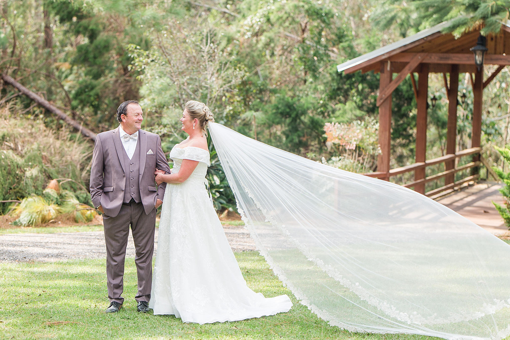 bride and groom laugh with bride's veil floating behind her