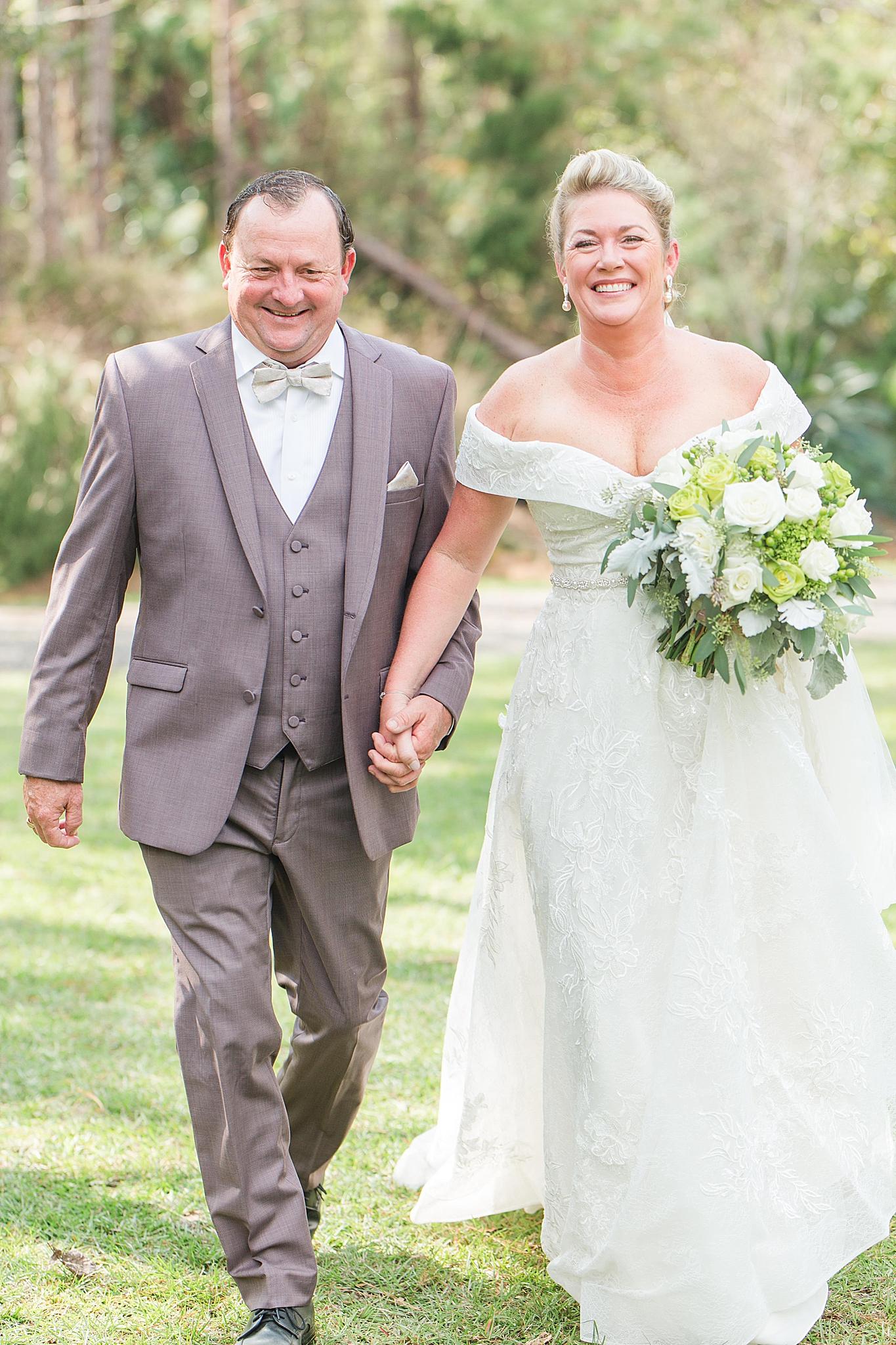 Alabama bride and groom walk through gardens in Loxley AL