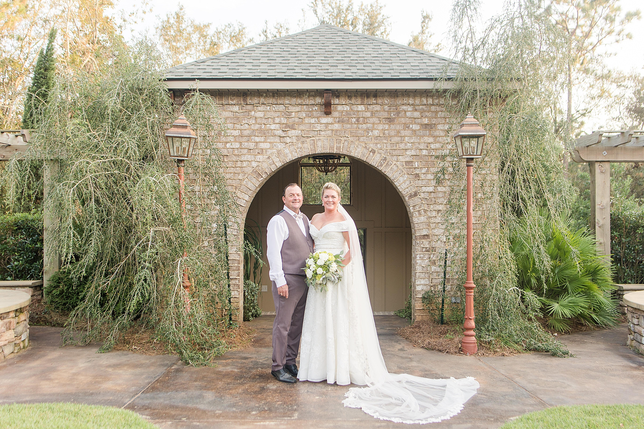 bride and groom pose by gate at Bella Sera Gardens
