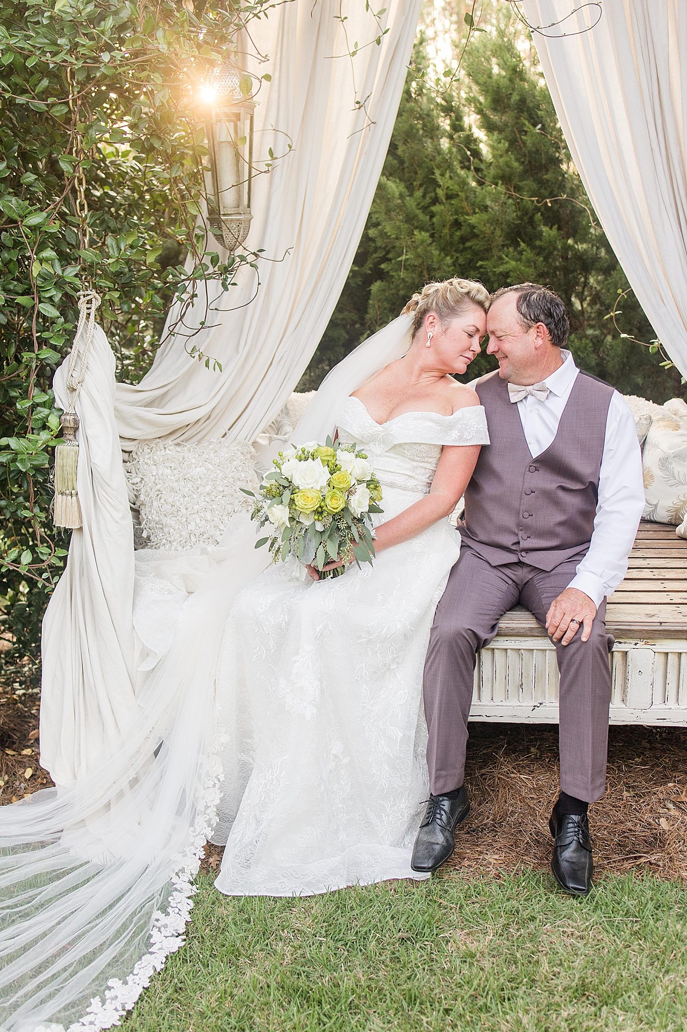 bride and groom sit on bench before Alabama wedding