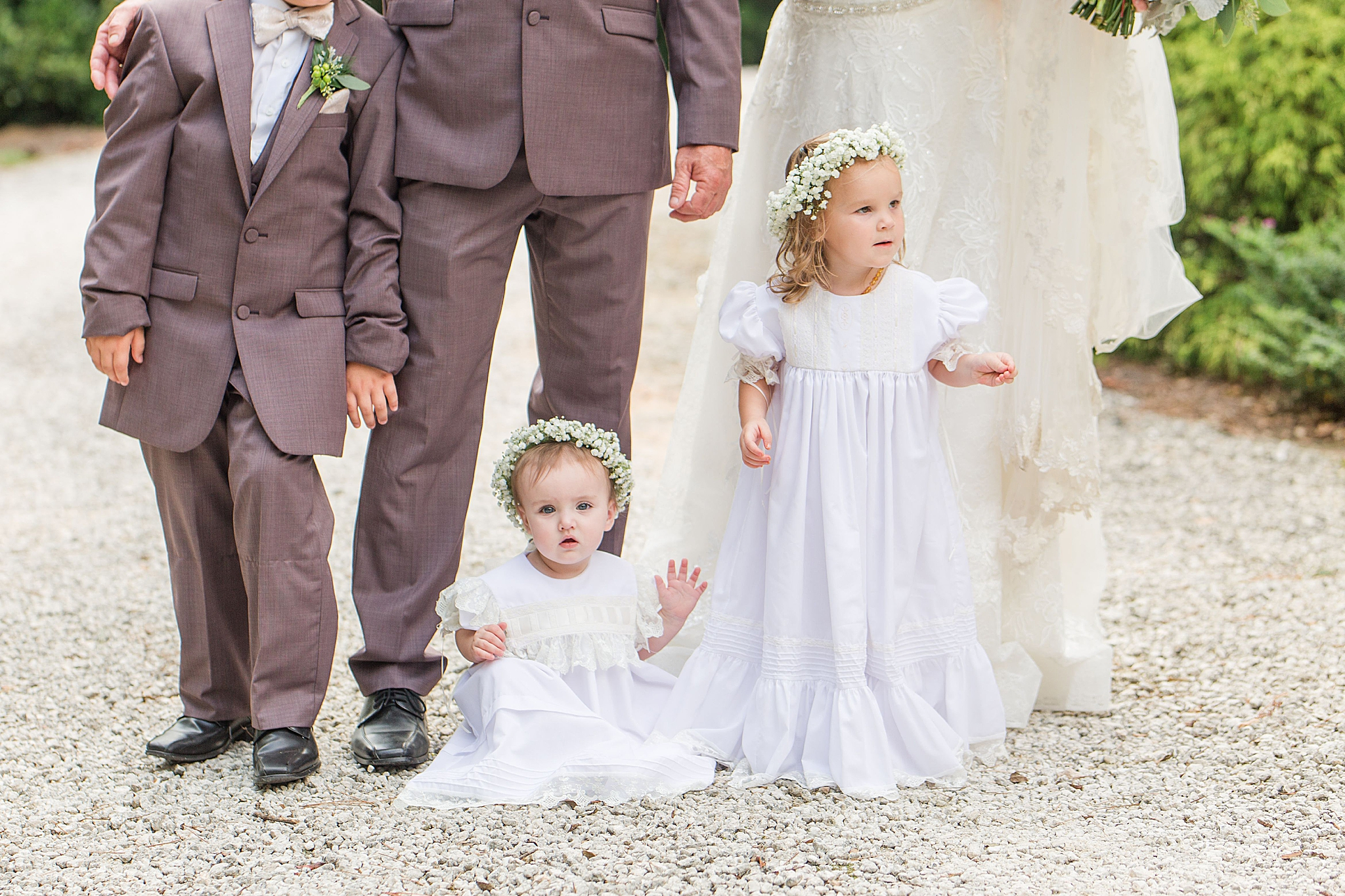 bride and groom pose with flower girls