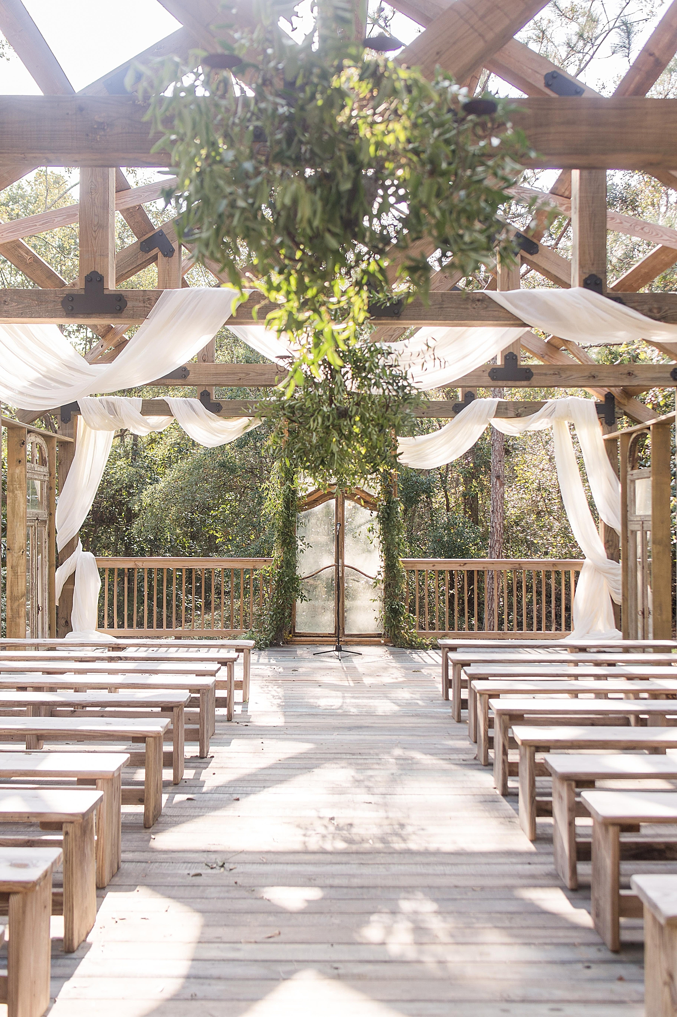 open air chapel decorated with simple white hangings and greenery at Bella Sera Gardens