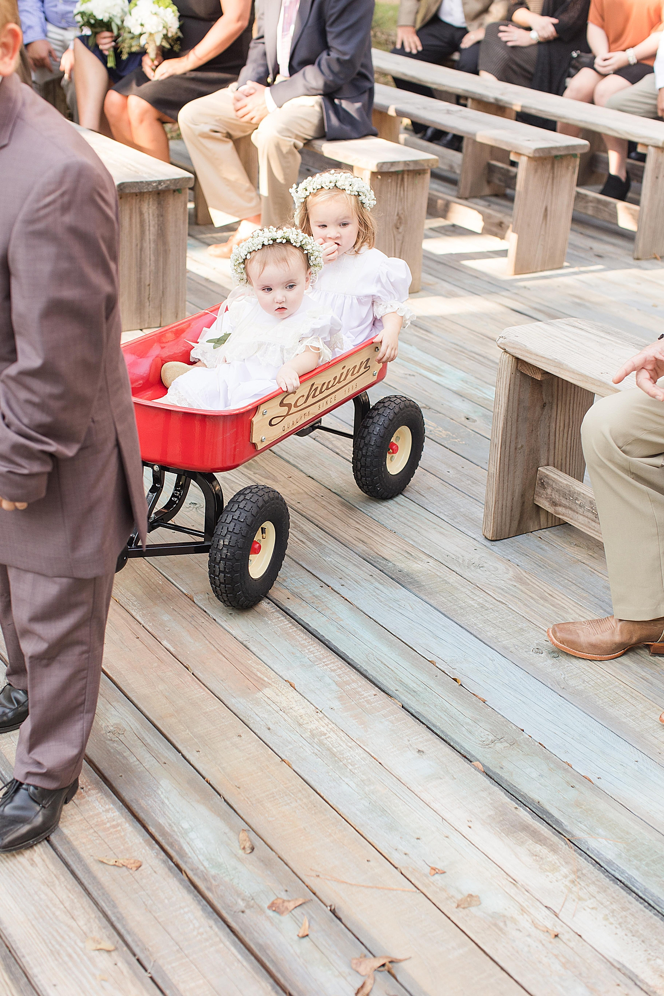 ring bearer pulls flower girls down aisle at Bella Sera Gardens