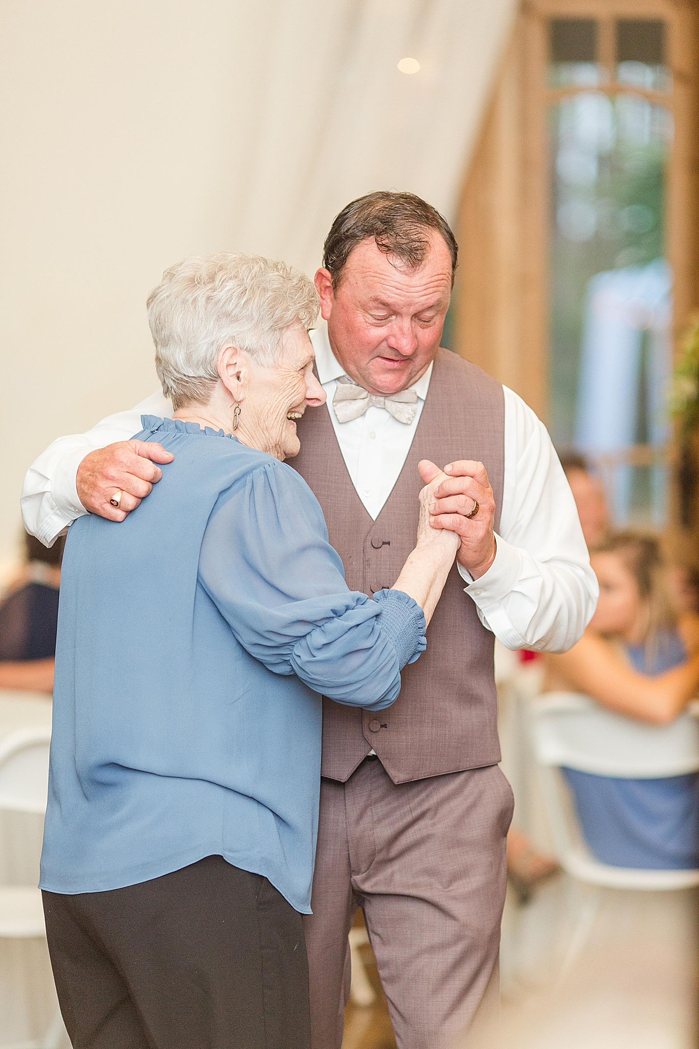 groom dances with mother during wedding reception