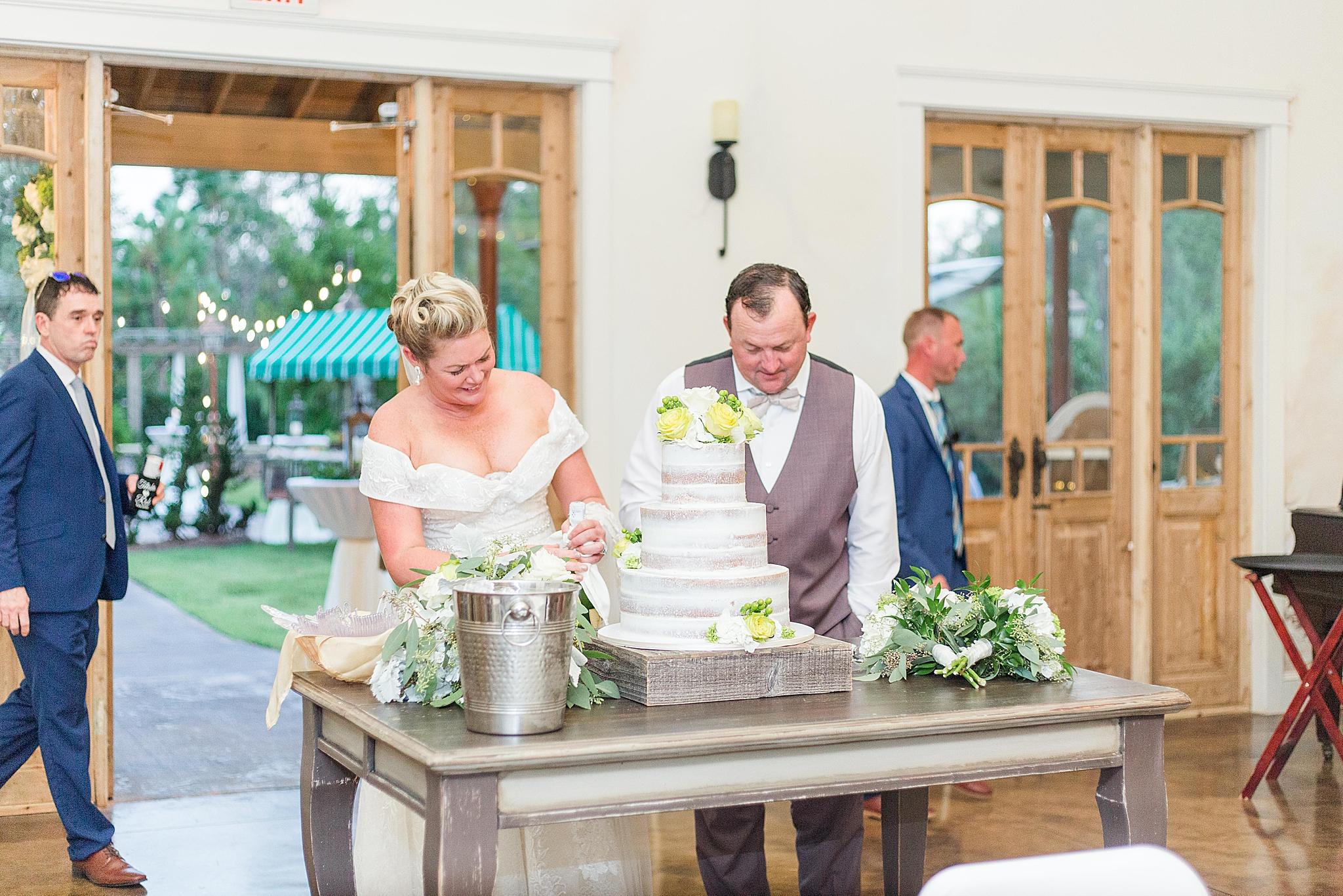 newlyweds cut wedding cake at Bella Sera Gardens