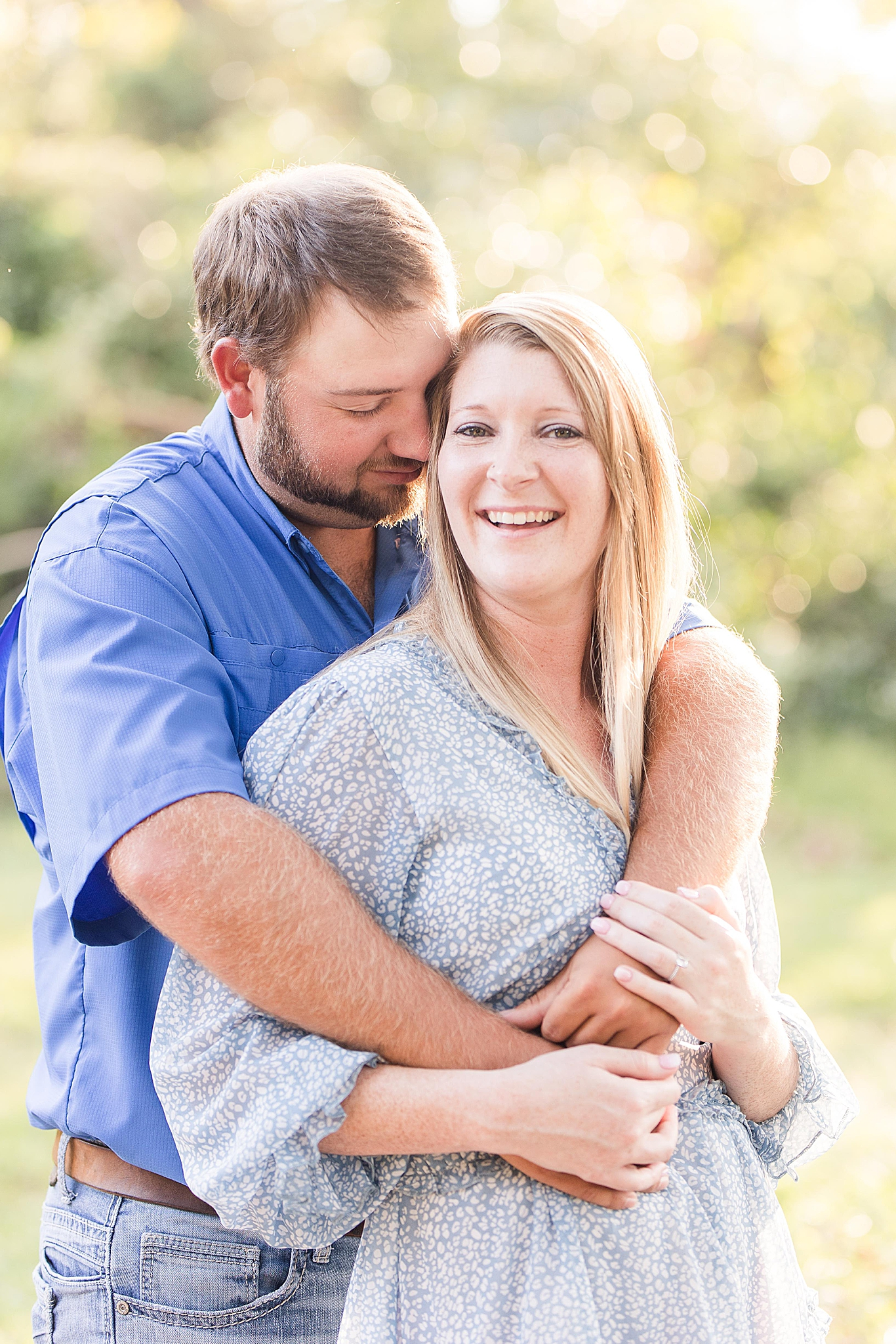 groom hugs bride from behind during Spring Hill College Engagement portraits