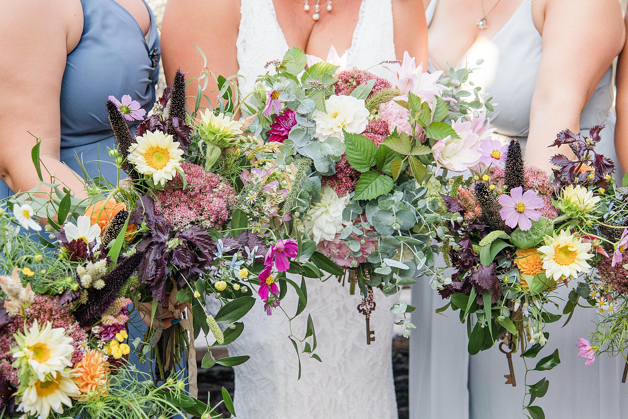 bride and bridesmaids hold wildflower bouquets