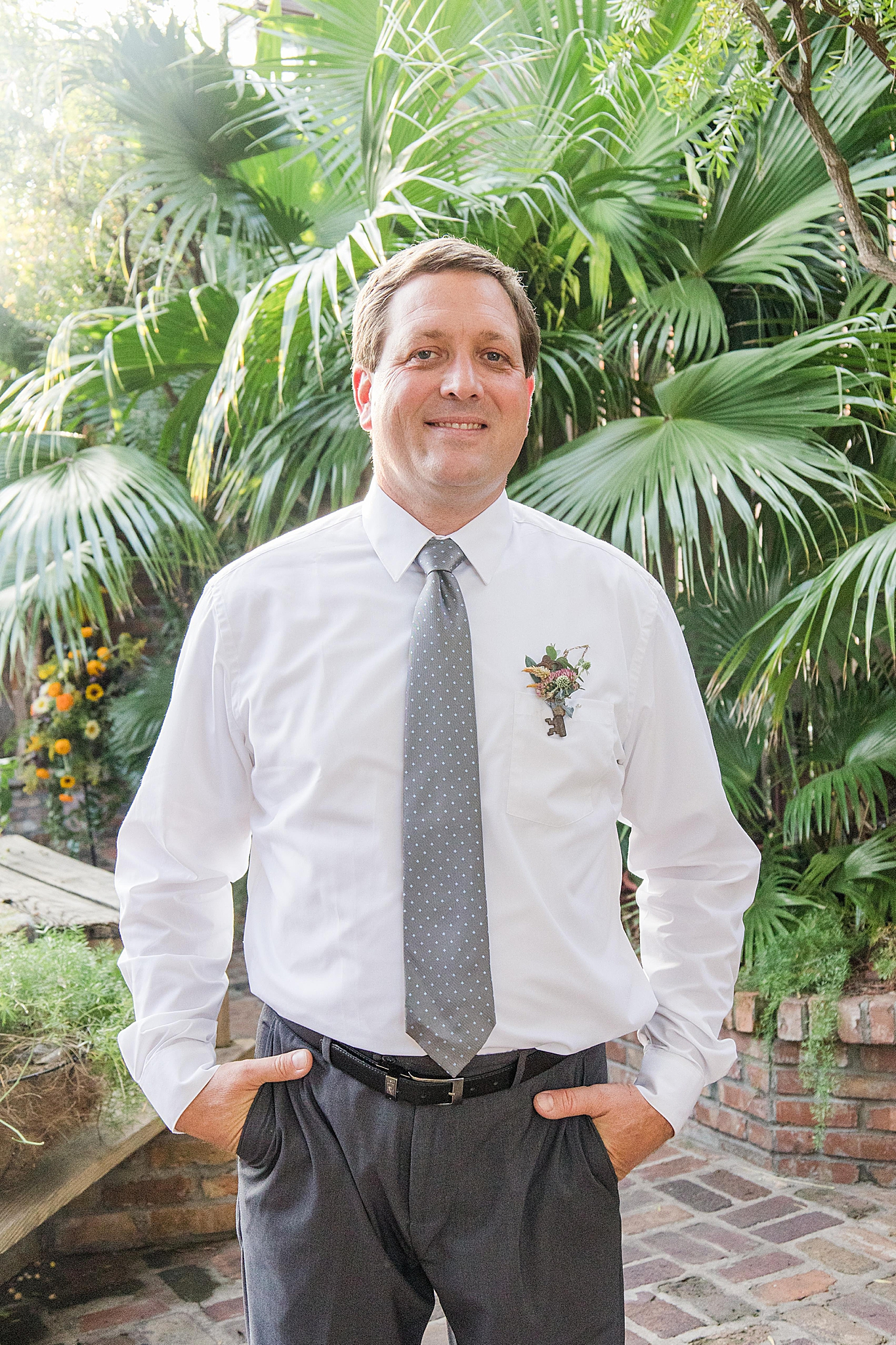 groom poses by palm trees in Florida