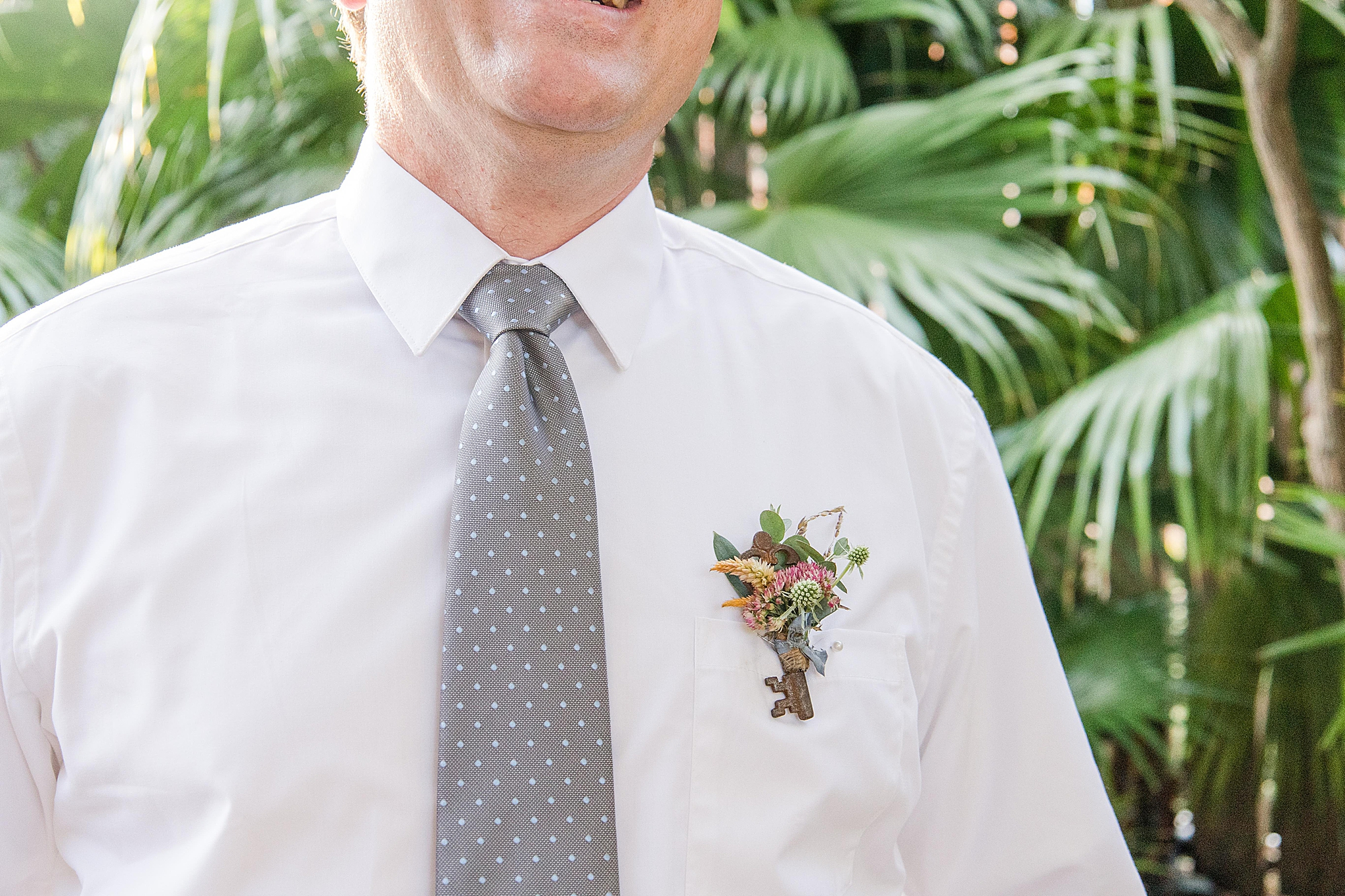 groom shows off wildflower boutonnière