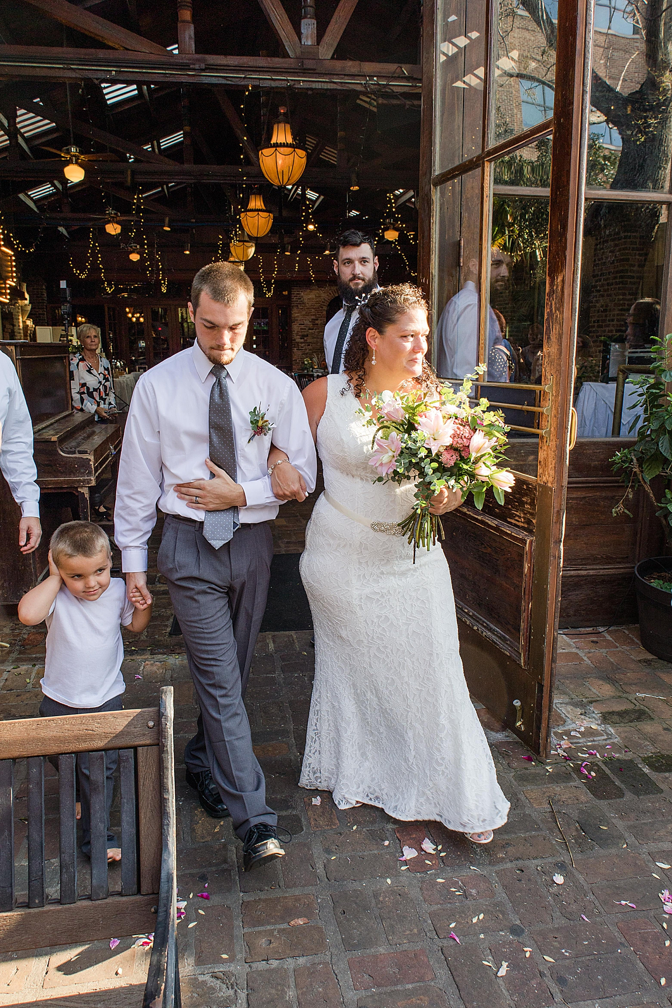 bride walks out to Seville Quarter wedding ceremony with son
