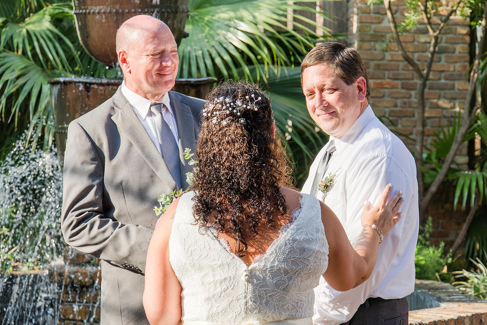 bride reaches groom for wedding ceremony at Seville Quarter