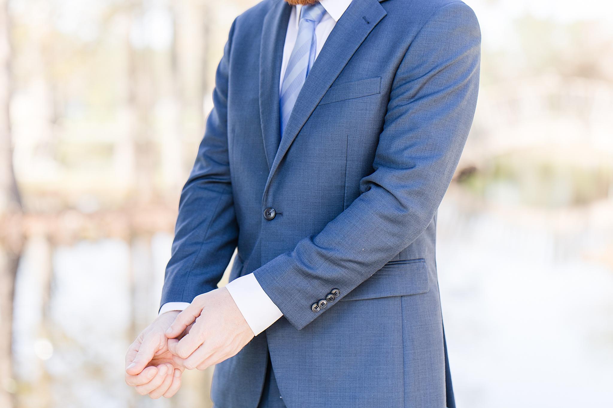 groom adjusts suit sleeves